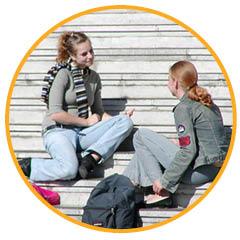 twee puber meisjes zittend op een trap buiten in de zon